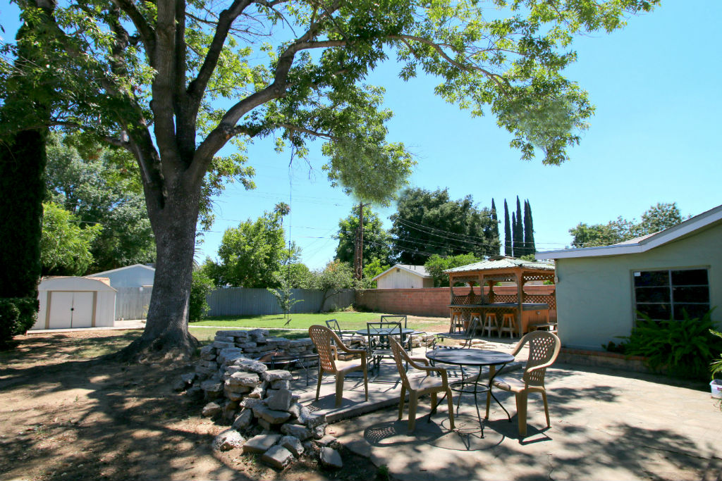 Open air patio for entertaining. Large mature shade tree with swing, shed, and above ground spa.