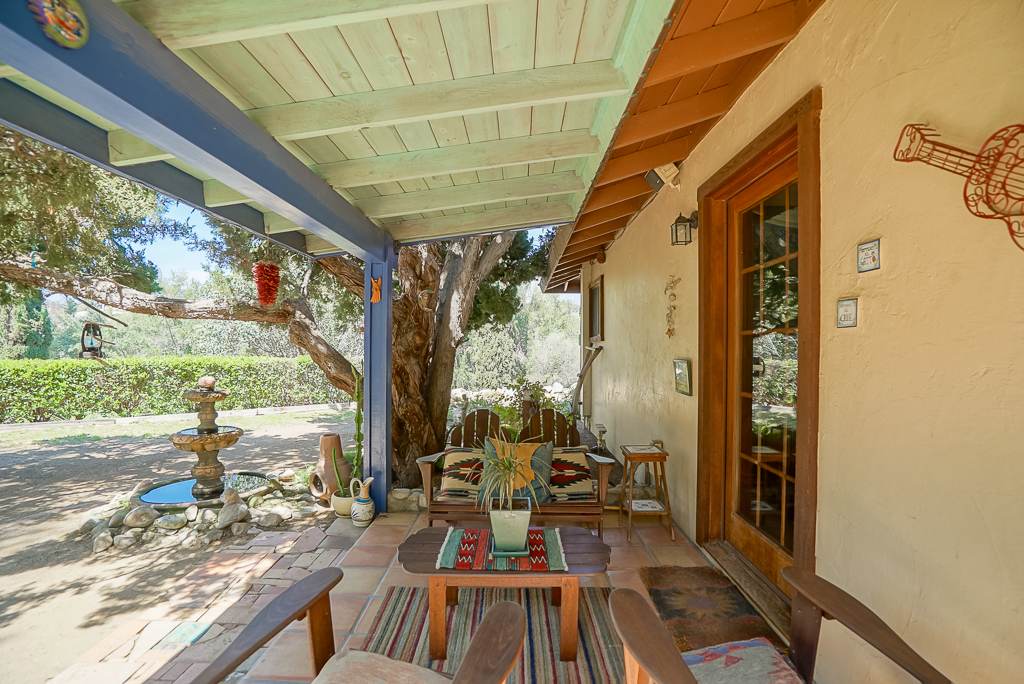 Covered patio outside the back bedroom next to a shade tree and soothing fountain.