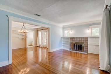 Standing at front door marveling at the gorgeous original hardwood floors and bookshelves flanking the fireplace.