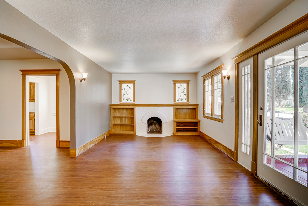 Living room with fireplace and newly laid laminate flooring (can easily be removed without harming original hardwood floors that are underneath).