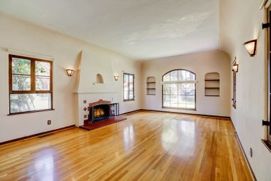 Look at this amazing living room with original hardwood floors, wood-burning fireplace, and tray ceiling.