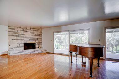 Living room with fireplace and gorgeous hardwood floors overlooking meditative backyard.