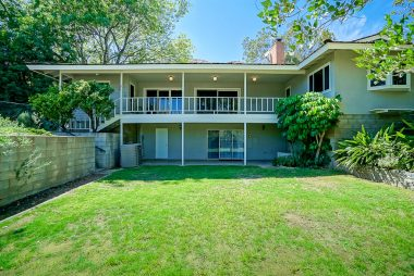Meditative back yard with garden area, mature shade tree, and RV parking.