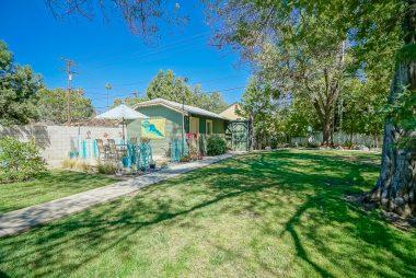 Dreamy backyard with shade tree, aviary, beachy patio area, and 1-car detached garage.