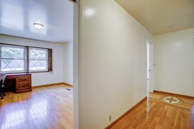 Bedroom #1 and hallway to other bedrooms, highlighting the gorgeous hardwood floors.