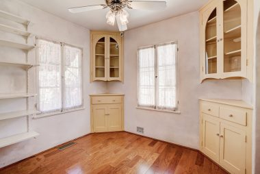 Breakfast nook with built-in corner hutches and newer wood floors.