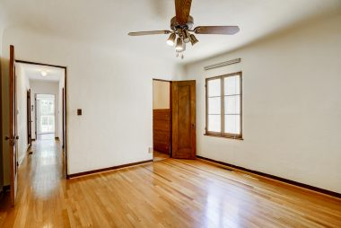 Alternate view of front bedroom with view into walk-in closet that boasts a built-in chest of drawers.