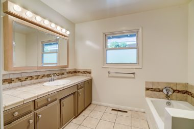 Hallway bathroom with separate shower stall in addition to a soaking tub.