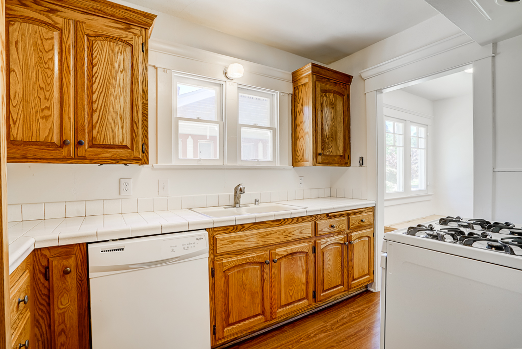 Kitchen with tile counter tops, gas stove, and adjacent breakfast nook.