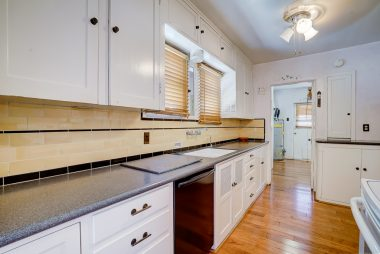 Kitchen with Corian counters, newer wood floors, dishwasher and lots of cabinetry.