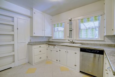 Alternate view of kitchen with dishwasher, spice rack, and original built-in ironing board. Refrigerator and stove included.