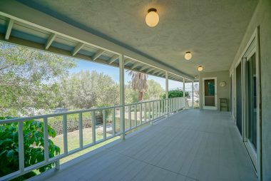 Upper extra-wide balcony patio right off the main living room area with two sets of newer sliders. At the end of the patio is the doorway to the kitchen, so imagine having breakfast overlooking the serene backyard and view of Riverside.