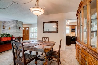 Formal dining area with view of doubledoor front entry and kitchen. This room also boasts gorgeous hardwood floors under the carpeting.