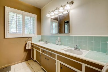 Bath with double sinks, retro counter tile, and newer tile floor.