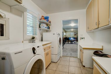 Spacious laundry room with lots of cabinetry, tile floor, and mop/cleaning storage too.