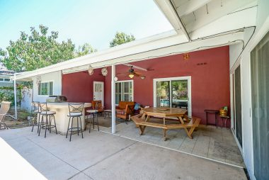Large covered patio with ceiling fan, builtin BBQ, three sets of double pane sliders, and view of in ground pool and gorgeous backyard!