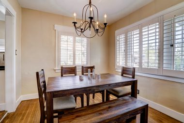 Formal dining room with chandelier and window shutters.