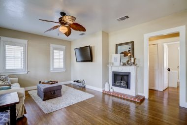 Alternate view of living room with hardwood floors, window shutters, ceiling fan, and fireplace (it's faux and it stays with house).