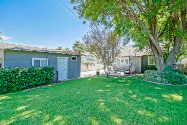 Photo taken from far back corner of yard shows the expansiveness of the yard with shade trees and room for a pool if desired.