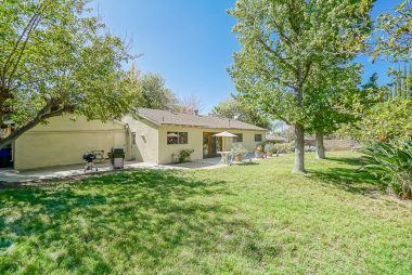 Pool-sized and private backyard with mature trees and an arroyo behind the fenced property.