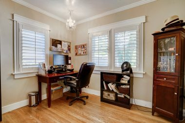 2nd of two bedrooms, currently being used as an office. Note the hardwood floors and window shutters.