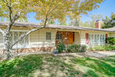 Mature shade trees, charming criss cross windows, and attached 2-car garage.