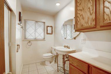 Spacious hallway bathroom with pedestal sink and tile flooring.