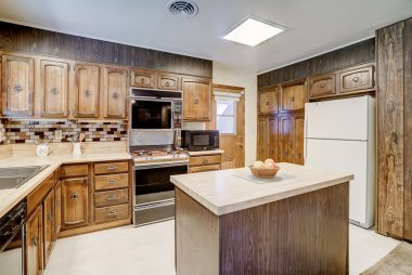 Original kitchen with lots of cabinetry dishwasher, double oven, and preparation island.