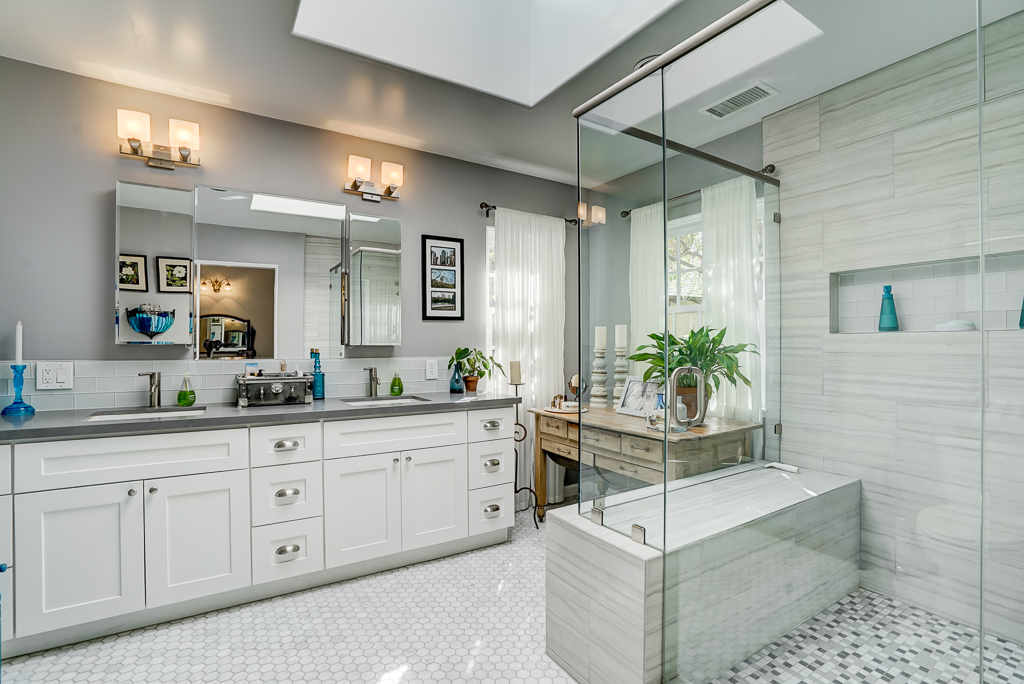 Remodeled Private Master Bathroom With Skylight, Glass Shower, Tile Floor,  And Dual Wash