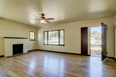 Spacious living room with refinished original hardwood floors, fireplace, and ceiling fan.