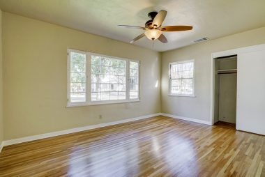 Front bedroom with refinished hardwood floors and ceiling fan.