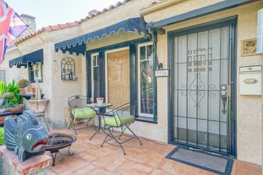 Charming tiled front porch with window awnings.