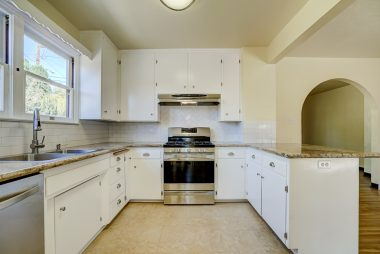 Remodeled kitchen with granite counters, stainless steel appliances, and tile flooring.