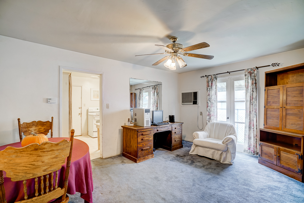 Formal dining room with ceiling fan and original French doors.