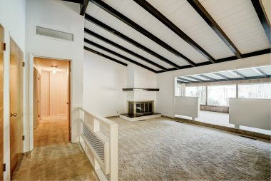 View from entry into step-down living room with beamed ceiling and corner fireplace, and the bonus room beyond.