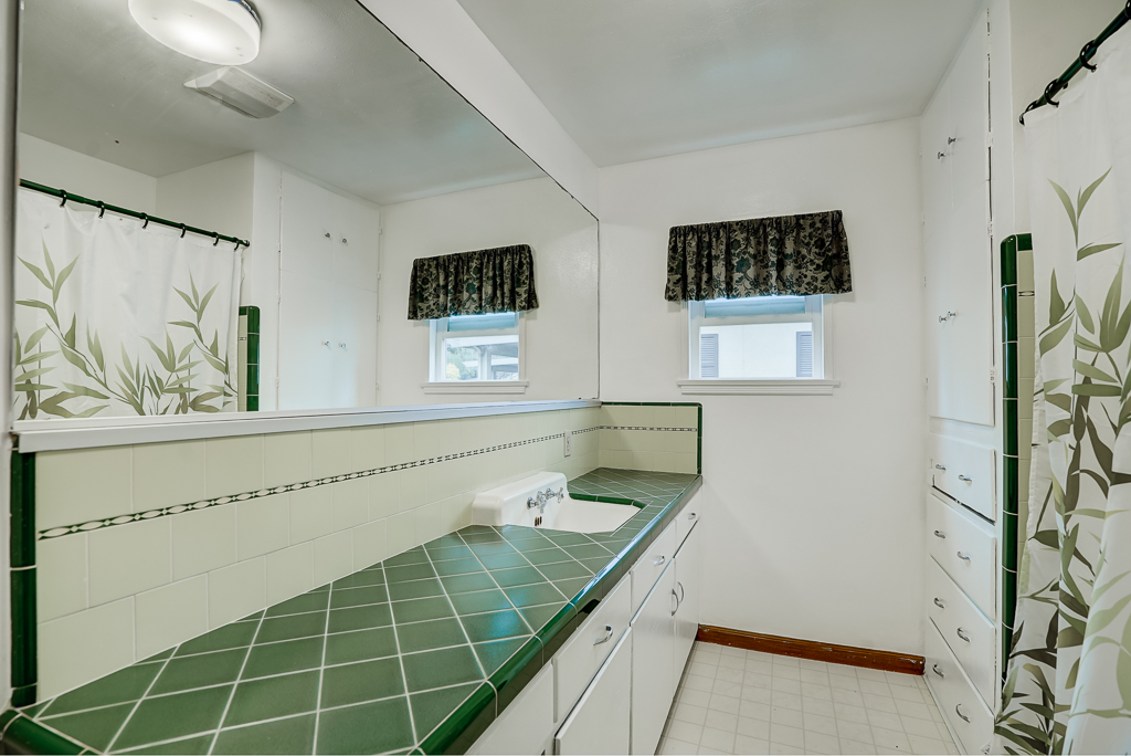 Bathroom with original green retro counter top tile and ribbon tile back splash, with space for additional sink if needed. Original tiled tub/shower enclosure too.