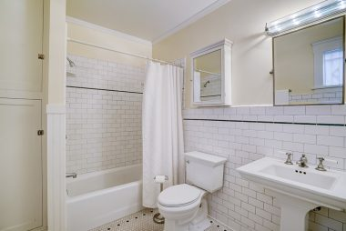 Downstairs bathroom with pedestal sink and subway tiled bathtub enclosure.