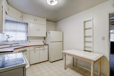 Light and bright kitchen with charming corner sink with original tile counter top and cabinetry, as well as built-in ironing board frame modified into spice rack.