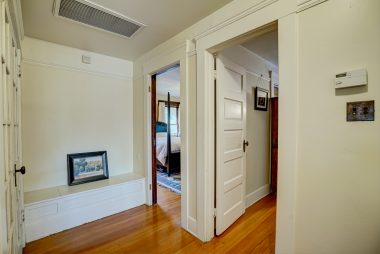 Upstairs landing with built-in storage seat and original push-button light switch.