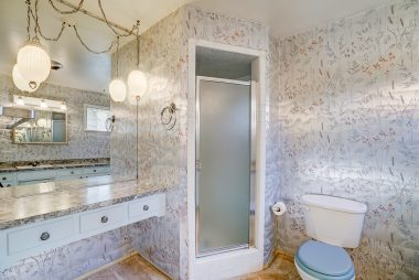 Private master bathroom with shower and original retro light fixture.