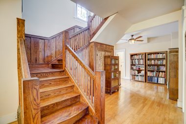 Exquisite staircase has been painstakingly refinished back to its original splendor, with view into the library.