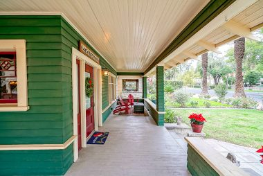 Spacious wraparound porch with wood ceiling.