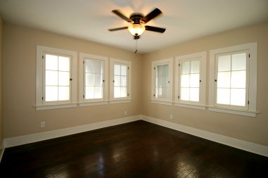 Back bedroom with ceiling fan and newer wood flooring.