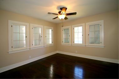 Front bedroom with ceiling fan and newer wood flooring.