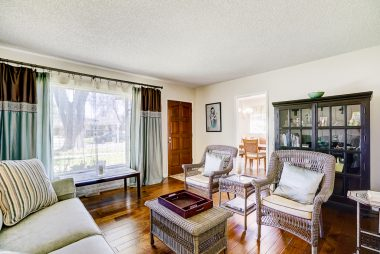 Living room with newer hardwood floors and large picture window overlooking gorgeous mature street trees.