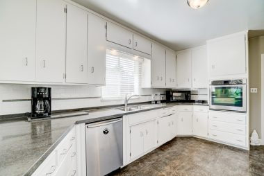 Gorgeous bright kitchen with Corian counter tops with newer appliances, including dishwasher.