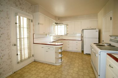 Original kitchen with corner sink and original tile and cabinetry.