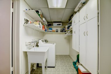 Separate indoor laundry room with utility sink and lots of cabinetry.
