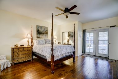 Huge master bedroom suite with separate French door entrance, mirrored wardrobe doors, ceiling fan, and newer hardwood floors.
