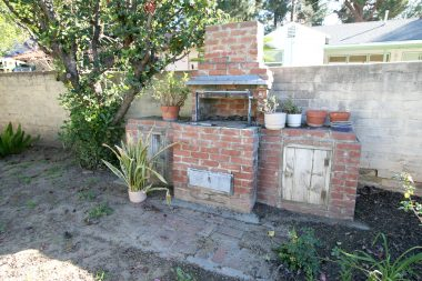 Original outdoor brick fireplace with privacy block wall.